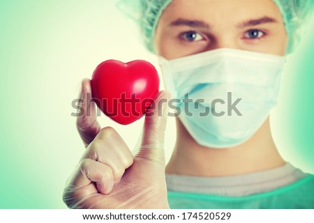 Handsome young male doctor holding heart shape toy
