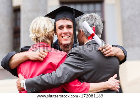 handsome young male graduate hugging his parents at graduation - stock photo