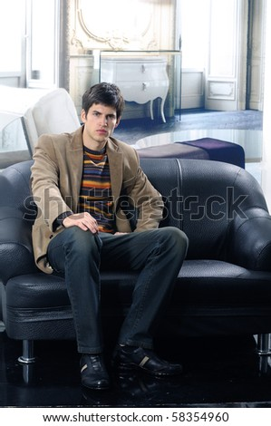 handsome young male model at interior seated on the couch