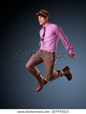 handsome young male model jumping - clean studio shoot, copy space - stock photo