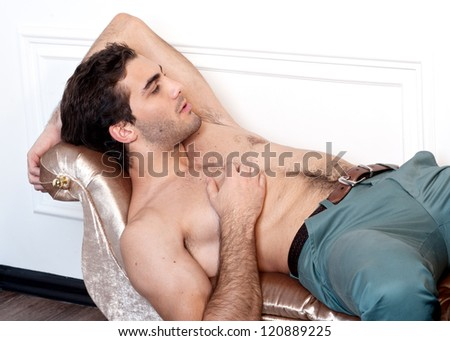 handsome young male model posing on sofa
