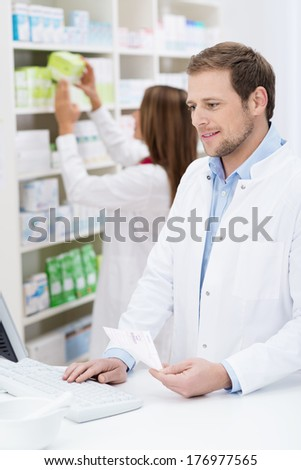 Handsome young male pharmacist checking a prescription on the computer with his female colleague checks supplies behind him - stock photo