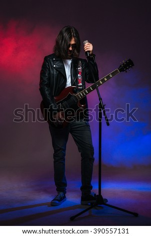 Handsome young male singer with long hair singing in microphone and playing guitar over colorful smoky background - stock photo
