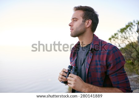 Handsome young male student looking out to the horizon while holding binoculars outdoors in nature