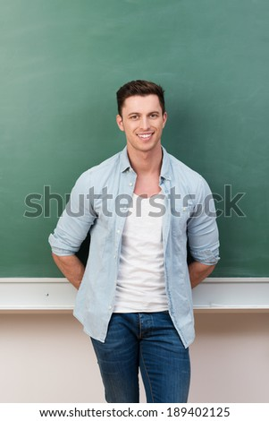 Handsome young male student standing relaxing against a green blackboard with his hands behind his back smiling at the camera