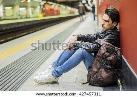 Handsome young male traveler in train station with backpack, looking to a side - stock photo