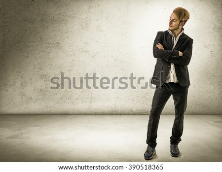 Handsome young man against brick wall - stock photo