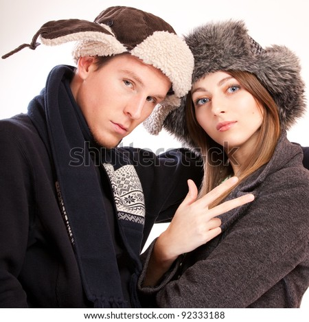 Handsome young man and beautiful girl in ear-flapped hats. Victory sign hand gesture.