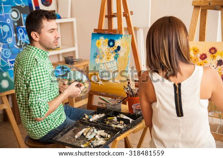 Handsome young man and women comparing their paintings while studying at an art school - stock photo
