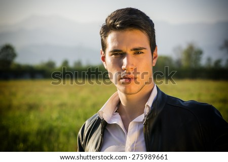 Handsome young man at countryside, in front of field or grassland, wearing white shirt and jacket, looking at camera - stock photo