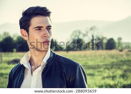 Handsome young man at countryside, in front of field or grassland, wearing white shirt and jacket, looking away to a side - stock photo