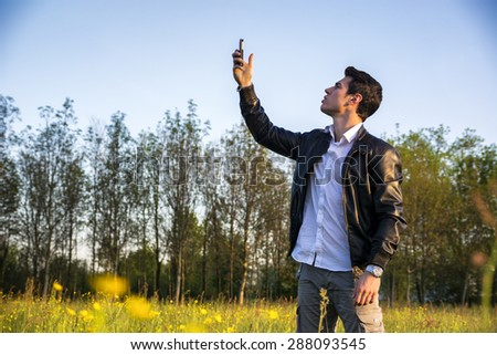 Handsome young man at countryside, using cell phone, standing in  field or grassland, wearing white shirt and jacket