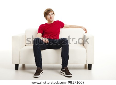 Handsome young man at home sitting on the couch - stock photo