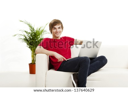 Handsome young man at home sitting on the couch and working on the laptop - stock photo