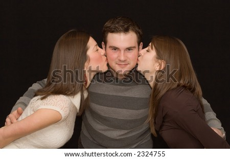 Handsome young man being kissed by two pretty girls.