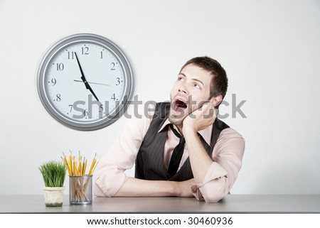 Handsome young man bored at the end of the workday - stock photo