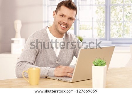 Handsome young man browsing internet at home, smiling, looking at camera. - stock photo
