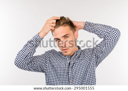 handsome young man brushing his hair - stock photo