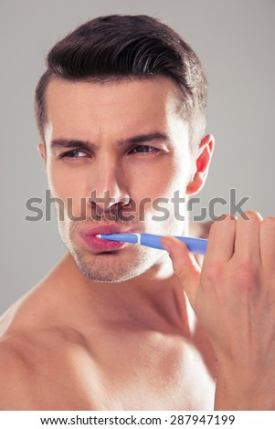 Handsome young man brushing teeth over gray background and looking away