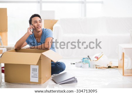 Handsome young man calling on the phone when packing his belongings - stock photo