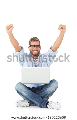 Handsome young man cheering at camera with laptop sitting on floor on white background - stock photo