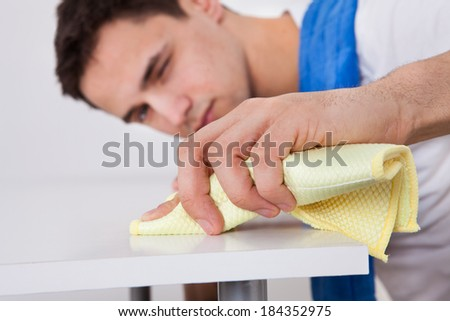 Handsome young man cleaning table with napkin at home - stock photo