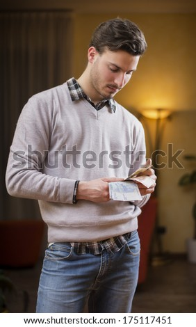 Handsome young man counting money, standing at home in his living room - stock photo