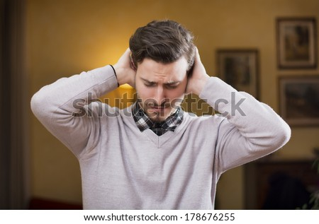 Handsome young man covering his ears, stressed or unhappy because of too much noise. Indoors shot - stock photo