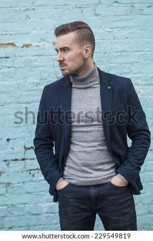 handsome young man dresses in jeans and blue blazer posing against painted blue brick wall