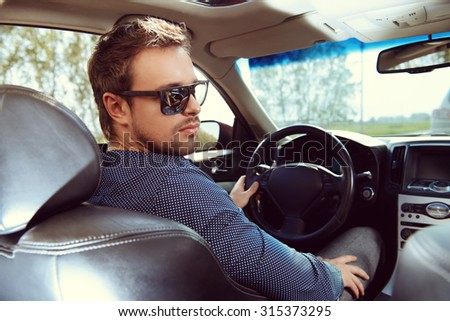 Handsome young man driving a car.  - stock photo