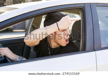 Handsome Young Man Driving a Car and showing the middle finger to someone behind him