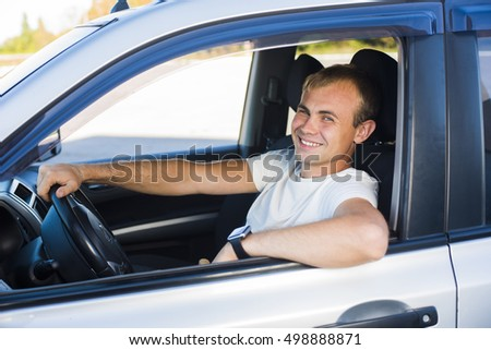 Handsome young man driving his car and smiling at camera