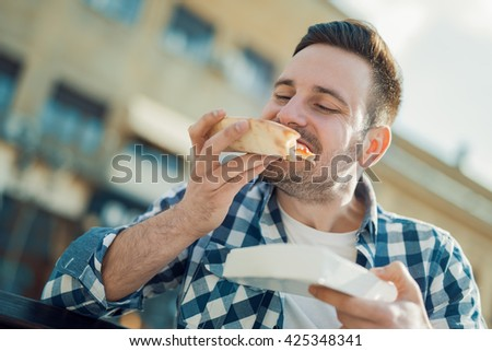 Handsome young man eating a slice of pizza outside on the street. - stock photo