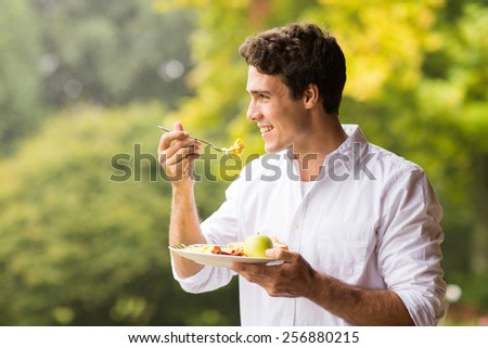 handsome young man eating scrambled egg for breakfast - stock photo
