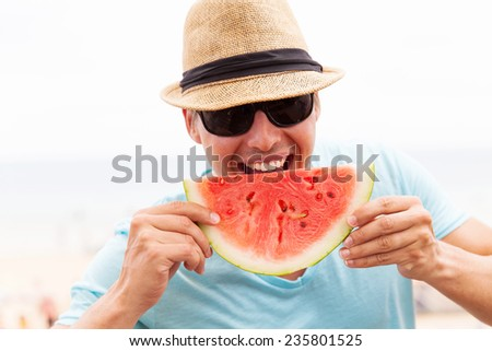 handsome young man eating watermelon on summer holiday - stock photo