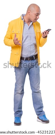 Handsome young man emotionally talks the mobile phone. He is also gesticulating with both hands. Looks slightly displeased. Full length portrait isolated on white background. - stock photo