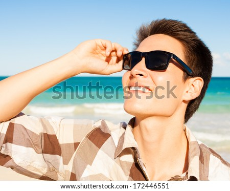 Handsome young man enjoying a summer day at the beach - stock photo