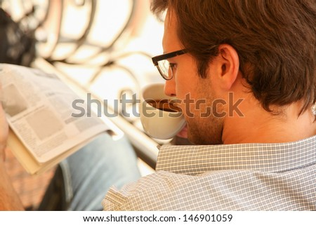 Handsome young man enjoying in cafe reading newspapers and drinking coffee.  - stock photo