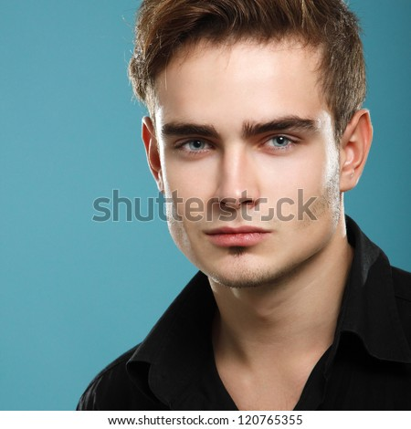 handsome young man face closeup, sexy guy looking at camera, studio shot over blue - stock photo