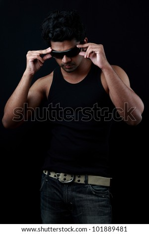 Handsome young man fixes his sunglasses in a dark background - stock photo