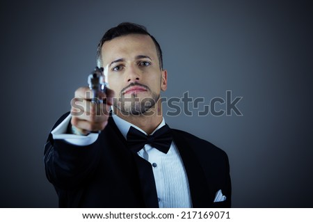 Handsome young man gangster police spy agent assissin holding and pointing a gun wearing a suit - stock photo