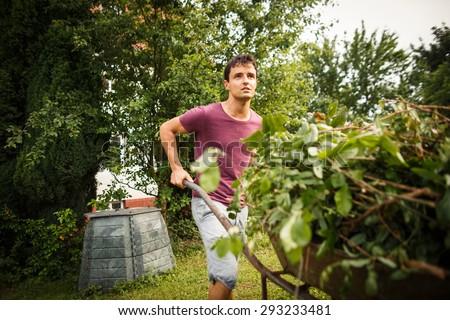 Handsome young man gardening in his garden - stock photo