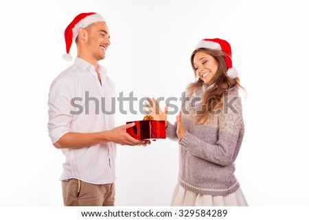 handsome young man giving a Christmas present to his girlfriend