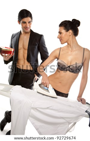 Handsome young, man giving a gift to a gorgeous woman in lingerie who is ironing his shirt - stock photo