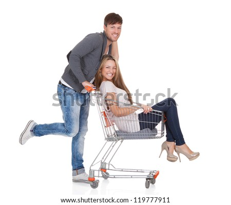 Handsome young man going out to shop pushing his carefree laughing wife along in a shopping trolley or cart as they have a fun day out - stock photo
