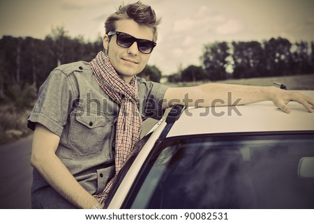Handsome young man having summer trip on a car. - stock photo