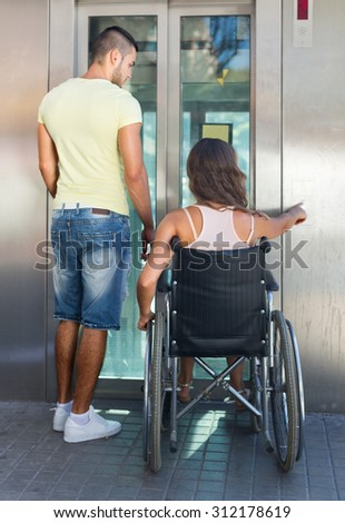 Handsome young man helping handicapped girlfriend at outdoor elevator