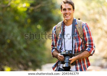 handsome young man hiking in mountain valley with dslr camera - stock photo