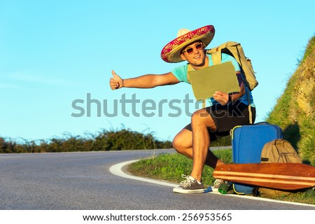 Handsome young man hitch-hiking along a rural mountain road. Hiker guy with luggage and longboard try to stop a car holding paper with copy space. - stock photo