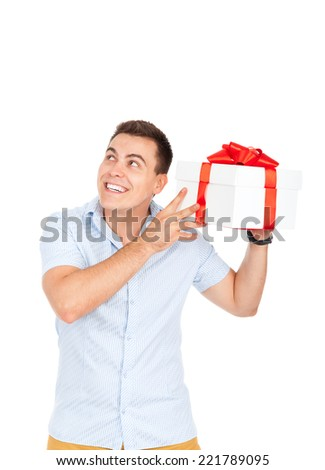 Handsome young man hold gift box smile look up to empty copy space, isolated over white background - stock photo